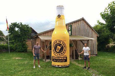 Apfelwein-Süß-gespritzt-aufblasbare-Flasche-Easy-Inflate-AD-vor-Hütte