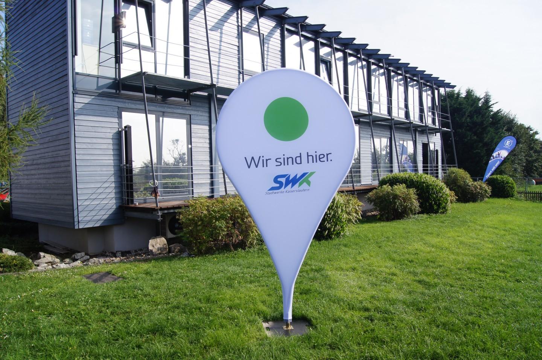 Sonderprojekte-Standortmarker-vor-Entdecker-Hauptzentrale-auf der-Wiese-bei-Sonnenschein-im-Hintergrund-eine-Beachflag-Easyflag-Drop