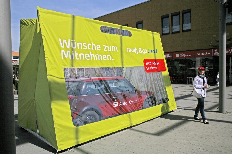 Eine-Tüte-für-ein-Auto-steht-in-der-Fußgängerzone-bei-Sonnenschein-mit Fenster-zum-durchschauen-für-unseren-Kunden-Sparkasse-Sonderanfertigung