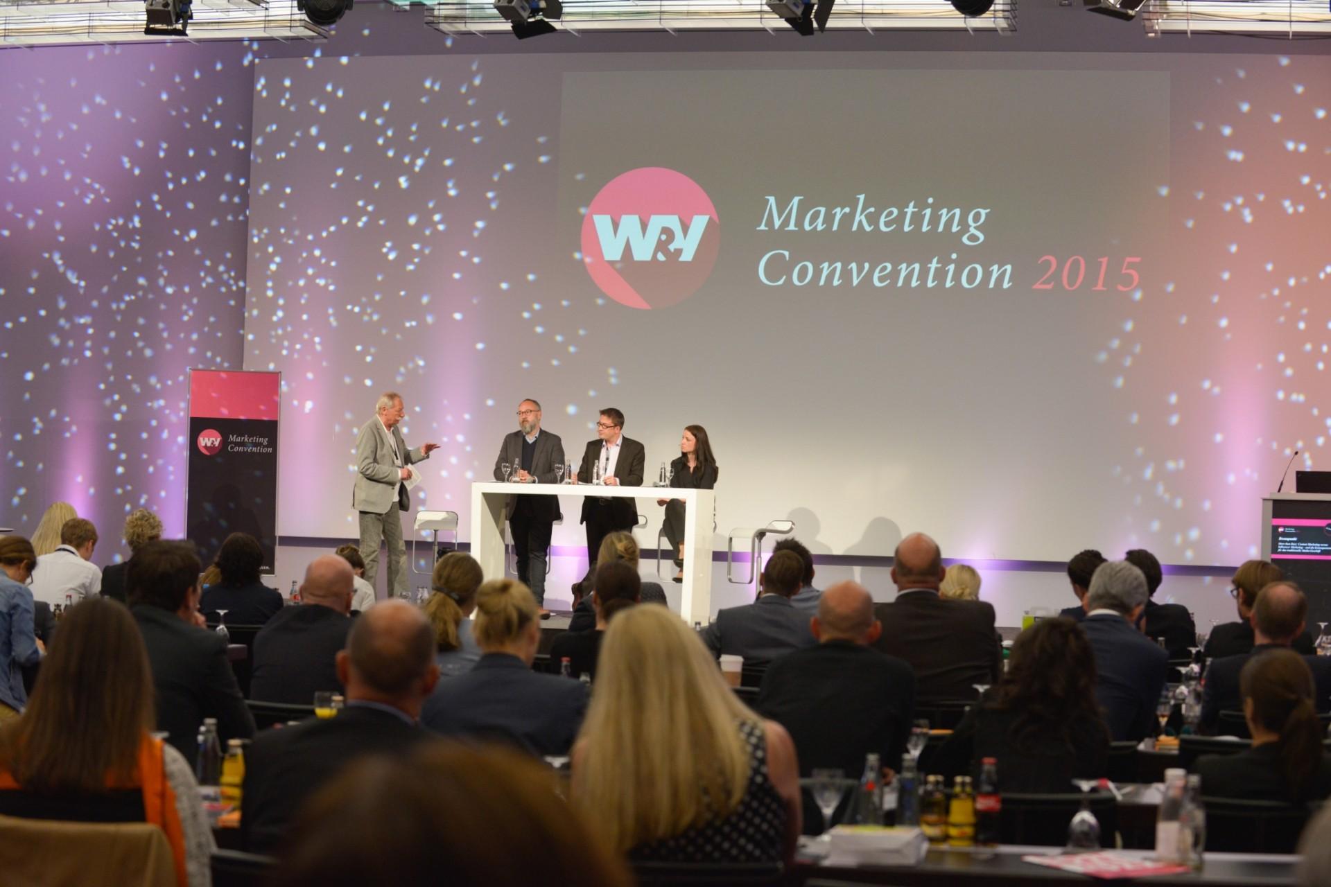 Marketing-Convention-2015-Vortrag-auf-Bühne-vor-vollem-Foyer-mit-unserem-Aufsteller-Roll-Up-Easymag-und-Aufkleber-Easysticker